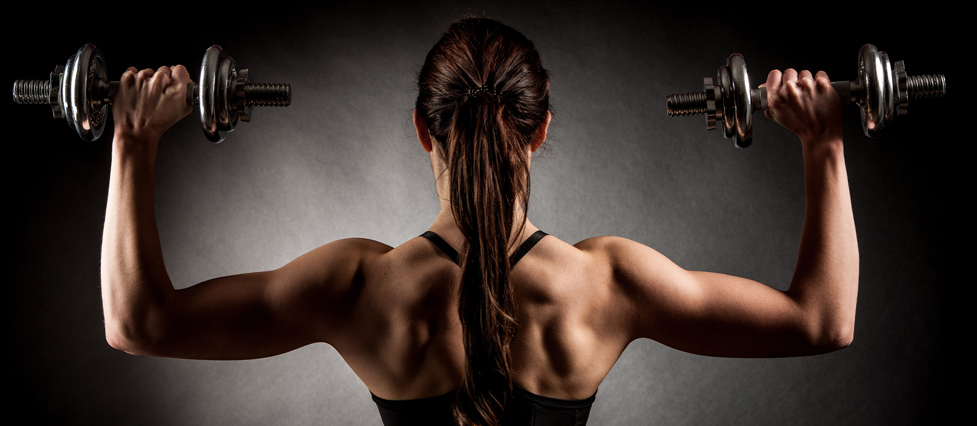 a female athlete with dumbbells in her hands showing her back muscles